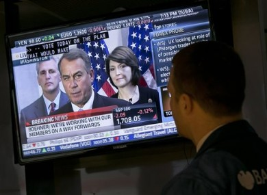 Specialist Frank Masiello watches a television monitor on the floor of the New York Stock Exchange showing a Washington news conference by House Speaker John Boehner