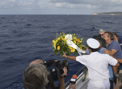 Fishing boat captain Calosero Spalma throws a wreath into the sea to pay tribute to the victims of Thursday's migrant shipwreck
