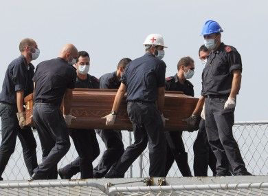 The casket of one of the migrants who died when their boat capsized in the Canal of Sicily is carried aboard an Italian navy ship on Saturday.