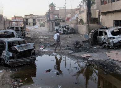 An Iraqi inspecting the aftermath of a bombing in Baghdad's al-Jadidah district