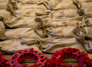 Sandbags, filled with soil from the World War I battlefields of Flanders, are piled next to poppy wreaths at the In Flanders Fields Museum in Ypres, Belgium.