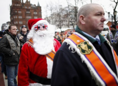 A demonstrator dressed as Santa walks with participants in today's march.