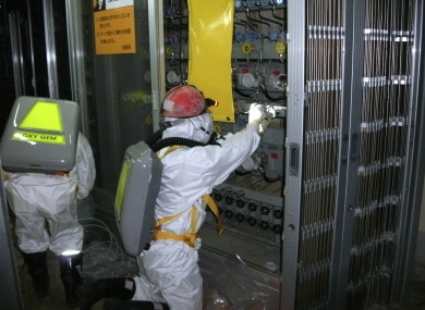 A worker measures water levels at the number one reactor of the Fukushima Daiichi Nuclear Power Station.