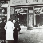 People stand outside a Jewish-owned shop in an unnamed German town, after the Kristallnacht.<span class=