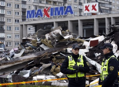 Policemen stand near a collapsed Maxima supermarket in Riga