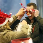 Barbara Connolly from Wicklow puts some novelty glasses on her daughter's boyfriend Rob<span class=