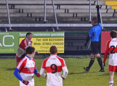Derry's Declan Mullan is shown a black card by referee Brendan Rice.