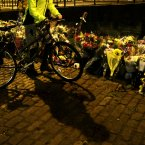 A cyclist  passes  flowers near to the Clutha bar helicopter crash scene in Glasgow. PRESS ASSOCIATION Photo. Picture date: Tuesday December 3, 2013. See PA story ACCIDENT Helicopter. Photo credit should read: Andrew Milligan/PA Wire<span class=