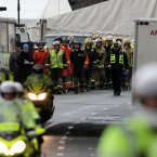 Members of the emergency services prepare to form a guard of honour as the wreckage of the police three-tonne Eurocopter is taken away by lorry after being lifted from the Clutha Vaults in Glasgow following the crash which killed at least nine people.<span class=