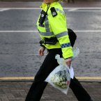 A police officer leaves flowers as the wreckage of the police three-tonne Eurocopter is taken away by lorry after being lifted from the Clutha Vaults in Glasgow following the crash which killed at least nine people.<span class=