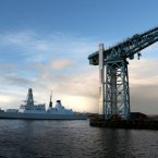 HMS Defender travels past the Titan Crane as it makes its way up the River Clyde back to Glasgow.<span class=