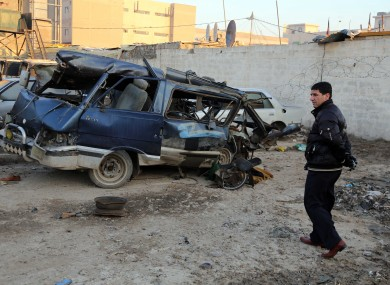 An Iraqi man inspects a minibus damaged in a car bomb attack in Baghdad earlier this month.