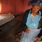 A woman plays traditional music forming part of the mourning process after death, inside her hut in Qunu.<span class=