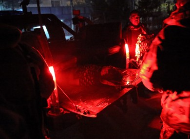 An Afghan man lies injured on a military vehicle at the site of the suicide attack