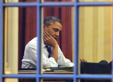 President Barack Obama works at his desk in the Oval Office.