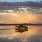 The sky is reflected on the Uyuni Salt Flats as a car drives by in Uyuni, Bolivia. <span class=