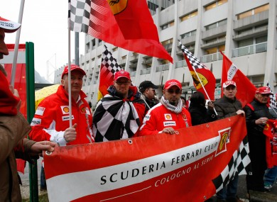 Supporters of Michael Schumacher hold Ferrari flags and a banner, to honour his 45th birthday, in front of the Grenoble hospital where the former seven-time Formula One champion is being treated.
