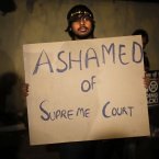 An Indian gay rights activist holds up a placard to protest against a recent Supreme Court verdict that upheld section 377 of the Indian Penal Code that criminaliSes homosexuality in New Delhi, India. The Supreme Court ruled that only lawmakers could change a colonial-era law that bans same-sex relations and makes them punishable by up to a decade in prison. <span class=