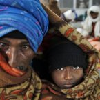 An elderly Indian man shares a blanket with his son as they wait at a railway station on a cold morning in Allahabad, India.<span class=
