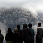 Villagers watch as Mount Sinabung releases pyroclastic flow during an eruption in Tiga Kicat, North Sumatra, Indonesia, Saturday. The 2,600-meter (8,530-foot) volcano has sporadically erupted since September. <span class=