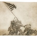 Five Marines and one Navy corpsman raise Old Glory on Mount Suribachi after taking Iwo Jima in 1945. <span class=