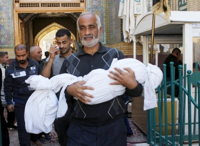 Ali Khalil carries the dead body of his 4-year-old son, Mohammed, who was killed in a bombing in the Shiite holy city of Najaf, 160 km south of Baghdad.