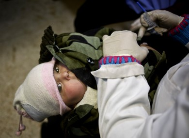 UNICEF nurse Nadine Houjairi removes the winter coat from a Syrian baby before giving the measles vaccine at the UN refugee agency's registration center in Zahleh, in Lebanon's Bekaa Valley.
