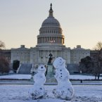 Snowmen sit in front of the Capitol in Washington.<span class=