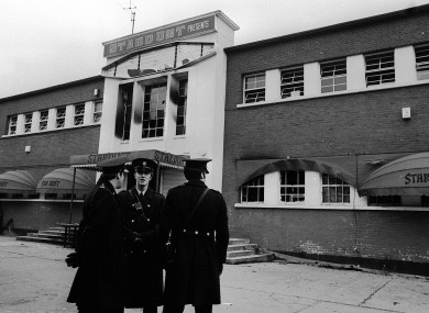 Gardai stand outside the main entrance of a fire-blackened Stardust Disco