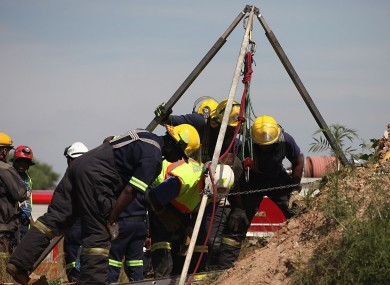 Emergency rescue workers attempt to free the trapped illegal miners.