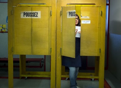 A Swiss voter leaves a polling box in Geneva yesterday