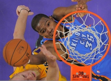 Oklahoma City Thunder small forward Kevin Durant, right, puts up a shot as Los Angeles Lakers center Chris Kaman defends .
