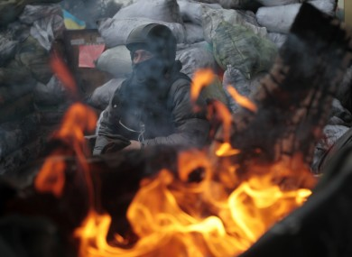 A protester guards the barricade in front of riot police in Kiev, Ukraine.