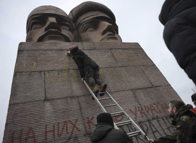 People paint on the KGB officers monument in Kiev