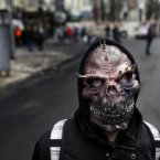 An anti-government protester wears a mask in central Kiev, Ukraine. <span class=