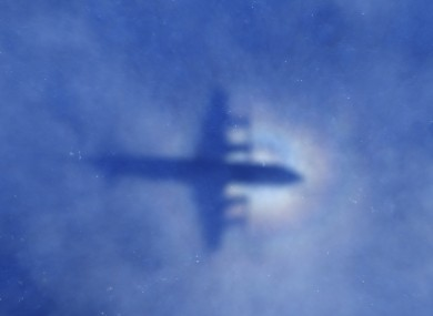 A shadow of a New Zealand Air Force aircraft is seen on low cloud cover while it searches for MH370.