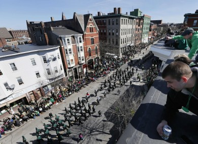 People watch the St Patrick's Day parade from a rooftop in Boston yesterday