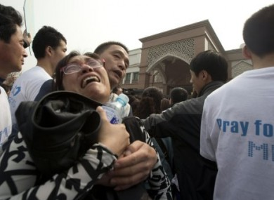A relative of Chinese passengers on board a missing Malaysia Airlines plane breaks down as she protests outside the Malaysia Embassy in Beijing.
