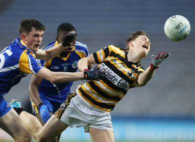 Colaiste Eoin's Conn O'Ceallachain is tackled by Brian Stack and Sam Omukoro of Marist College.