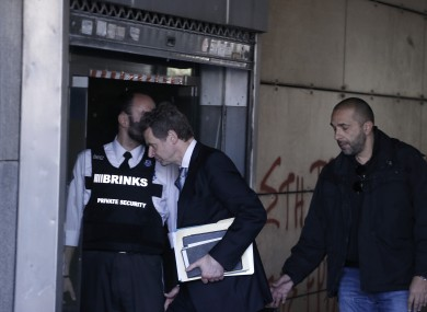 International Monetary Fund mission chief Poul Thomsen, center, escorted by a Greek plain clothed police man, enters the Greek Ministry of Finance in central Athens.