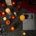 Candles are lit next to a letter reading