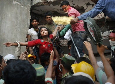 A Bangladeshi woman survivor is lifted out of the rubble by rescuers at the site of a building that collapsed. (File)