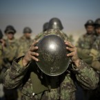 An Afghan army soldier adjusts his helmet as he lines up with others at a training facility in the outskirts of Kabul.<span class=