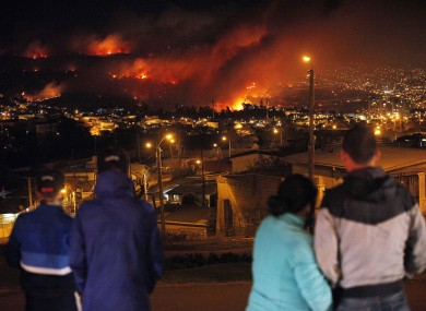 People watch as a forest fire rages towards Valparaiso.