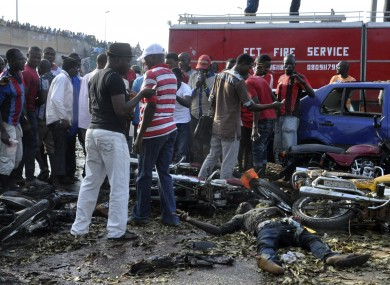 People gather at the site of a blast at the Nyanya Motor Park.