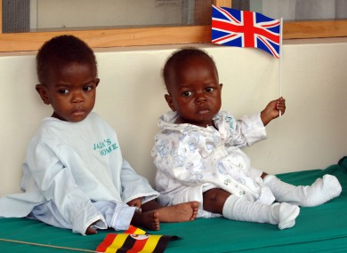 Two young children hold flags at Queen Elizabeth's visit to an AIDS orphanage in Kampala, Uganda.