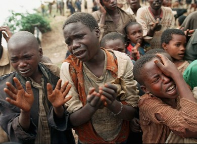 Rwandan refugee children plead with Zairean soldiers to allow them across a bridge separating Rwanda and Zaire where their mothers had crossed moments earlier before the soldiers closed the border on 20 August 1994.