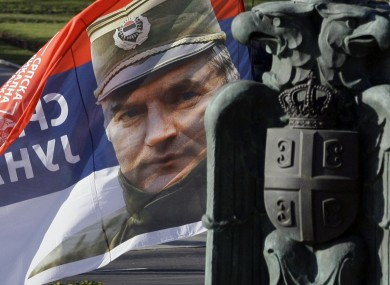A Serbian Radical Party supporter holds a flag with genocide suspect Ratko Mladic's picture. It reads, in Serbian:
