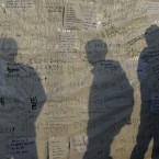 Visitors reading messages wishing safe return of missing passengers aboard the sunken ferry Sewol are silhouetted on the side of a tent at a port in Jindo, south of Seoul, South Korea. One by one, coast guard officers carried the newly arrived bodies covered in white sheets from a boat to a tent on the dock of this island, the first step in identifying a sharply rising number of corpses from the South Korean ferry that sank nearly a week ago. (AP Photo/Lee Jin-man)<span class=