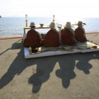 Buddhist monks pray for the safe return of passengers aboard the sunken ferry boat Sewol at a port in Jindo, South Korea. Divers made their way deeper Thursday into the submerged wreck of the ferry that sank more than a week ago as the death toll continues to rise and relatives of the more than 140 still missing pressed the government to finish the grim task of recovery soon. (AP Photo/Ahn Young-joon)<span class=